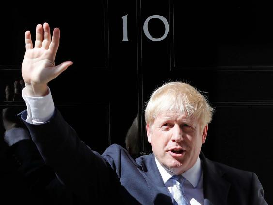 Boris Johnson waves from the steps outside 10 Downing Street at Downing Street (AP)