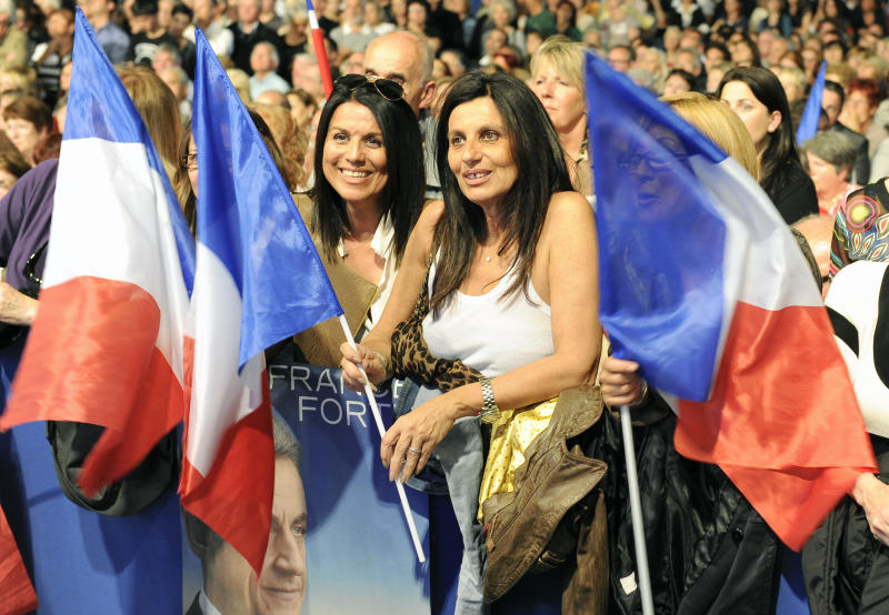 Supporters of France's President and candidate for the presidential elections, Nicolas Sarkozy hold french flags during a campaign meeting in Bompas, southern France, Saturday, April 14, 2012. The first round of the presidential elections will take place on April 22, followed by a second round on May 6. (AP Photo/Jean Paul Bonincontro)
