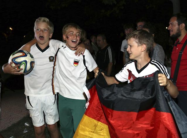 German children celebrate their team's World Cup victory against Argentina in Rio de Janeiro, Brazil, at the German Embassy in Ankara, Turkey, early Monday, July 14, 2014. Germany won the final by 1-0. (AP Photo/Burhan Ozbilici)