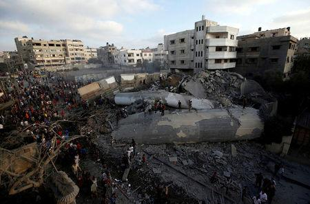 Palestinians gather around a building after it was bombed by an Israeli aircraft, in Gaza City
