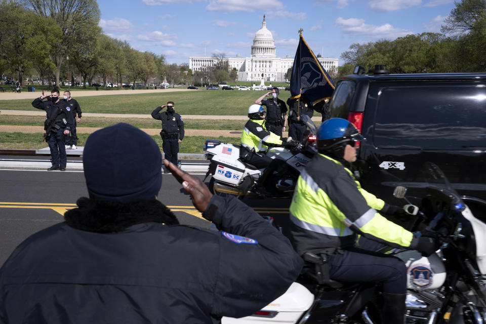 With the U.S. Capitol in the background, U.S. Capitol Police officers salute as procession carries the remains of a U.S. Capitol Police officer who was killed after a man rammed a car into two officers at a barricade outside the Capitol in Washington, Friday, April 2, 2021. (AP Photo/Jose Luis Magana)
