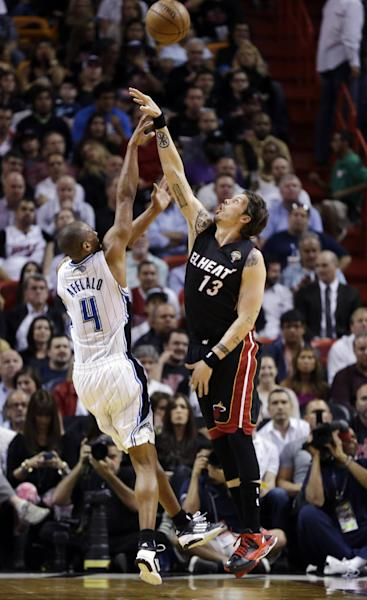 Orlando Magic's Arron Afflalo (4) shoots over Miami Heat's Mike Miller (13) during the first half of an NBA basketball game in Miami, Wednesday, March 6, 2013. (AP Photo/J Pat Carter)
