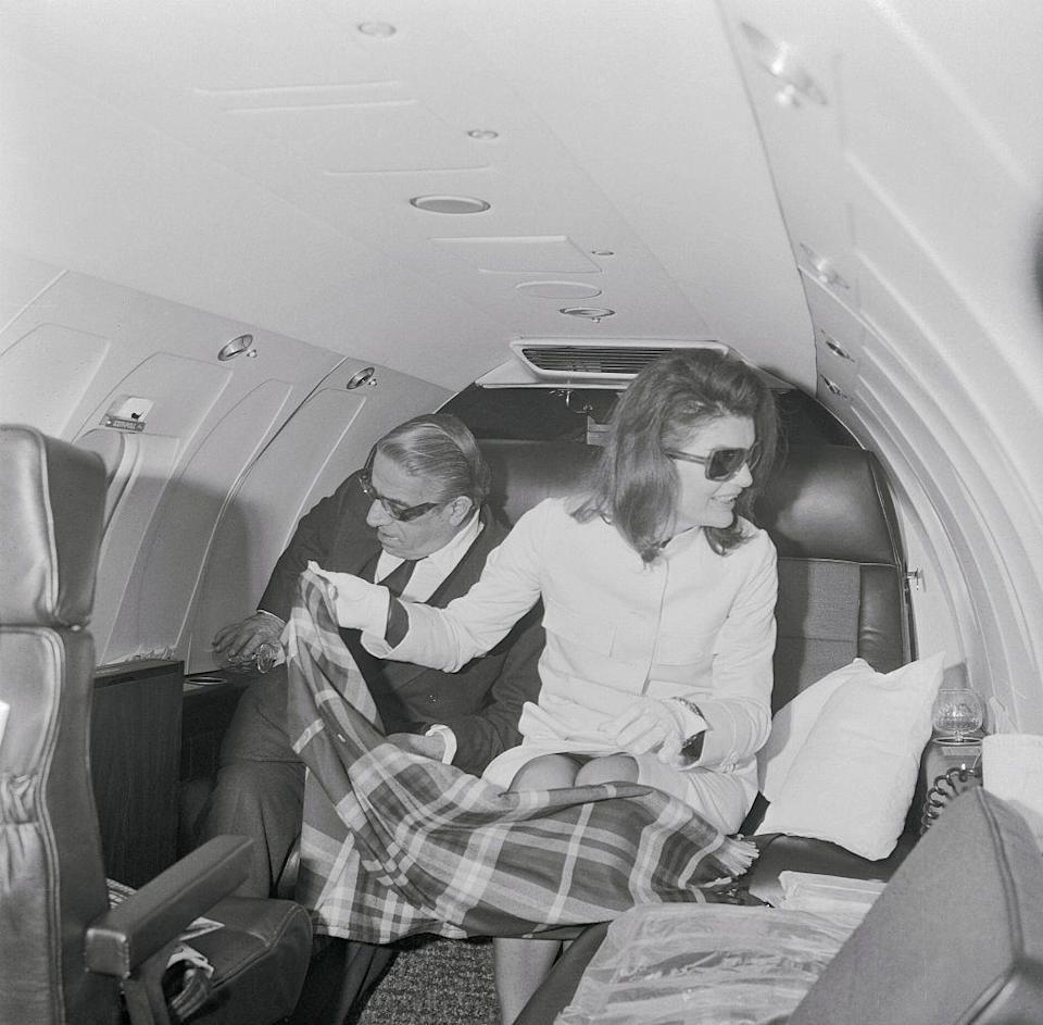 <p>Jacqueline Onassis wraps a blanket over her legs on a private jet in 1971.</p>