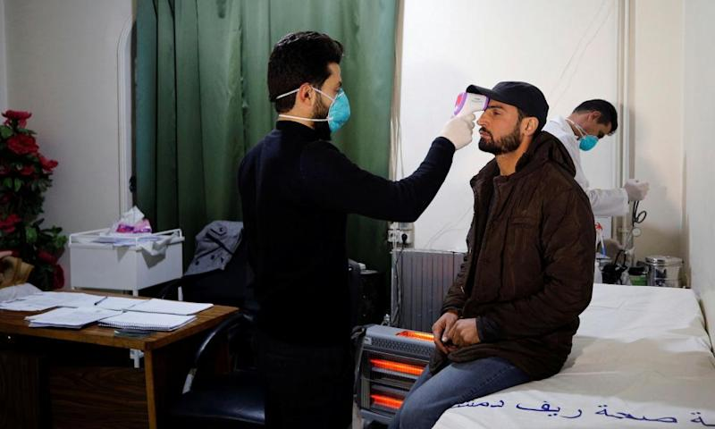 A passenger in Jdaydet Yabous, Syria, is tested for coronavirus at a border crossing with Lebanon.
