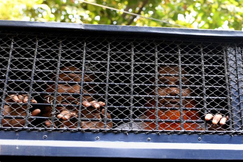 Accused of Holey Artisan Bakery attack are seen inside prison van as they are taken out of the court after hearing a verdict in Dhaka