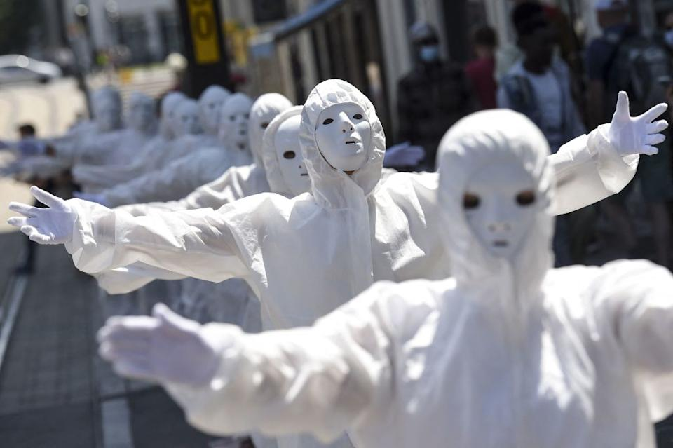 Performers, wearing a white mask and a protective outfit gesture during a demonstration against the new coronavirus safety measures including a compulsory health pass. Source: Getty