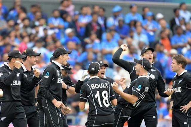 New Zealand's Martin Guptill (second right) celebrates with teammates after running out India's MS Dhoni at Old Trafford (AFP Photo/Dibyangshu Sarkar)