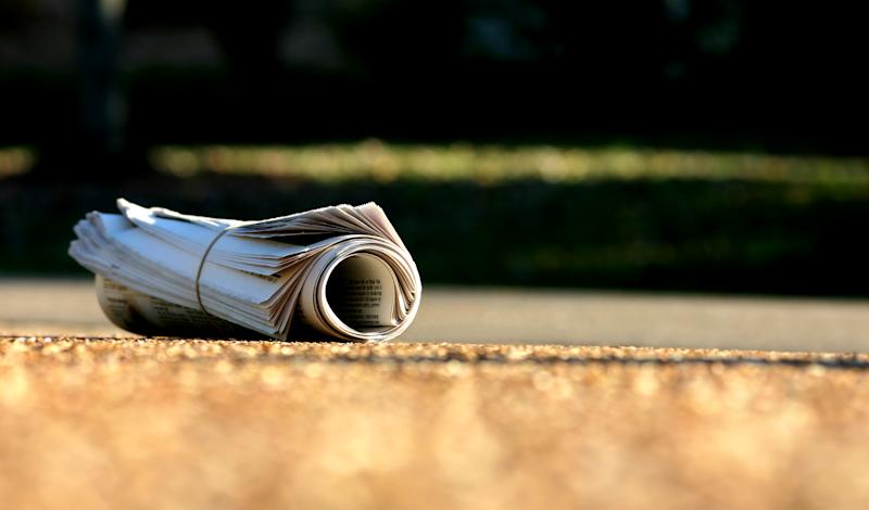 Image of newspaper rolled up on street as News Corp stops printing 100 regional mastheads