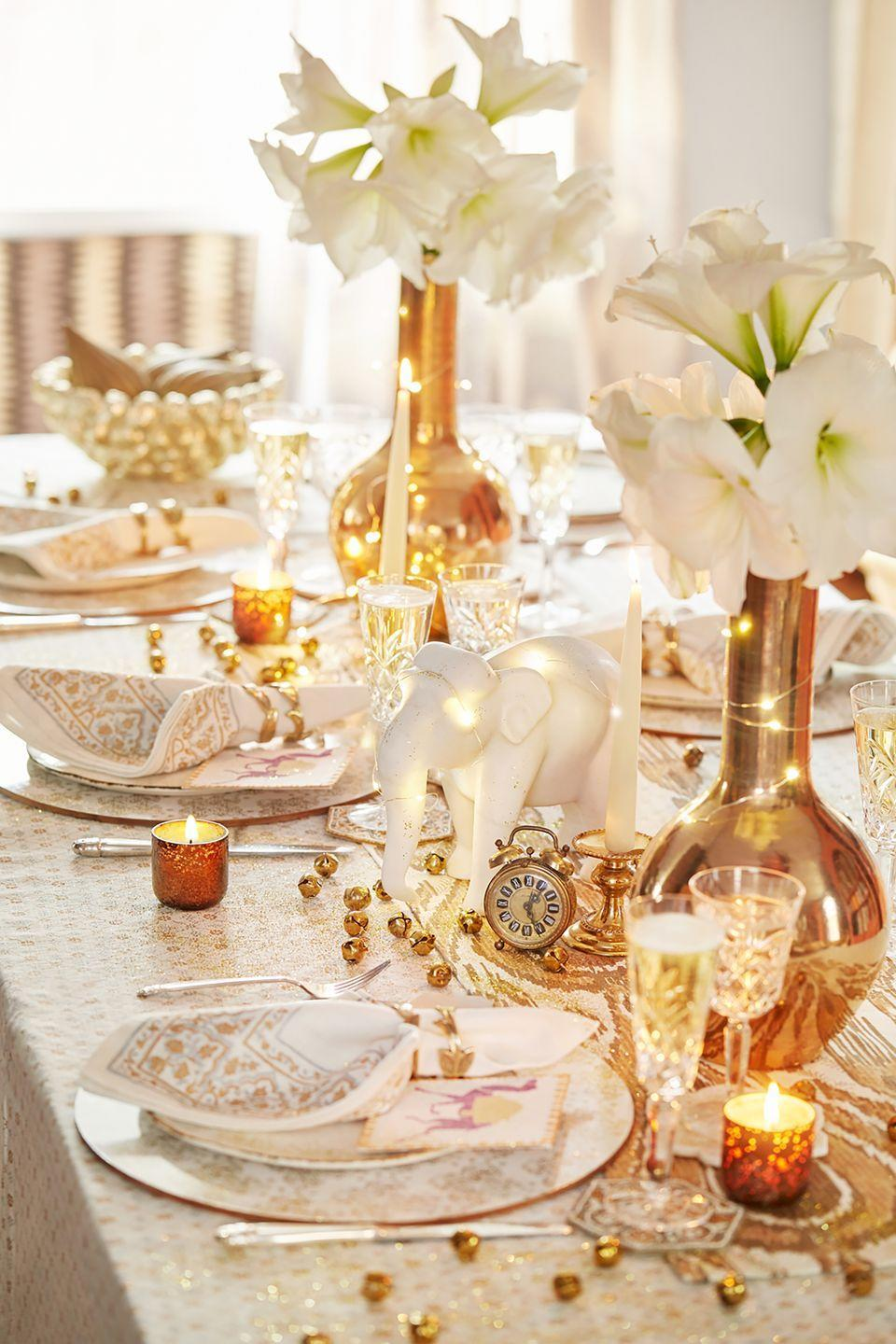 """<p>""""I like to incorporate quirky elements from my trips to create a fun table setting. I found these great porcelain elephants and a cool vintage clock on a recent trip to India. I also saw these tiny bells, which we scattered throughout the table to make it more festive."""" <em>—<a href=""""https://johnrobshaw.com/"""" rel=""""nofollow noopener"""" target=""""_blank"""" data-ylk=""""slk:John Robshaw"""" class=""""link rapid-noclick-resp"""">John Robshaw</a>, Textile Designer</em></p>"""