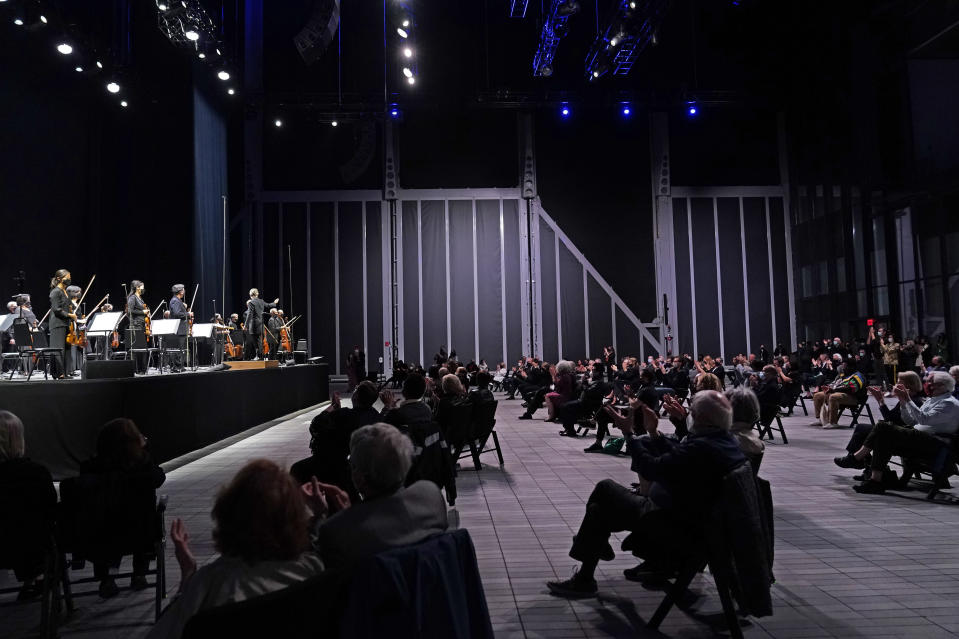 CORRECTS SPELLING OF FIRST NAME TO ESA INSTEAD OF ESSA - A live audience of spectators applauds as members of the New York Philharmonic stand after the orchestra performed a live concert together for the first time since March 10, 2020, at The Shed in Hudson Yards, Wednesday, April 14, 2021, in New York. Esa-Pekka Salonen, music director of the San Francisco Symphony and principal conductor of London's Philharmonia Orchestra, gestures from the stage. (AP Photo/Kathy Willens)