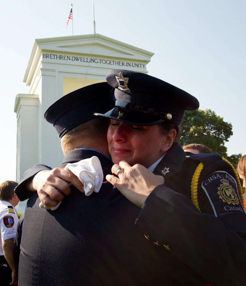 Canada Border Services officer Lisa Steel, right, hugs New York City fire department paramedic John Rugen after a 9/11 memorial service at the Peace Arch-Douglas border crossing in Surrey, British Columbia, on Sunday, Sept. 11, 2011. Hundreds of people gathered at the Canada-U.S. border to mark the 10th anniversary of the terrorist attacks of Sept. 11, 2001. (AP Photo/The Canadian Press, Darryl Dyck)