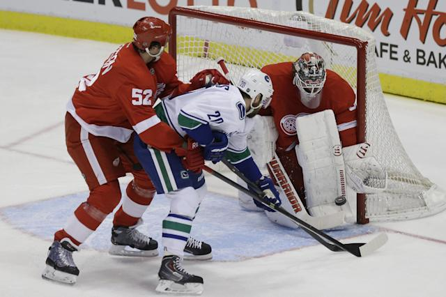 Vancouver Canucks left wing Chris Higgins (20), defended by Detroit Red Wings defenseman Jonathan Ericsson (52) of Sweden, shoots the puck at goalie Jonas Gustavsson (50) of Sweden during the first period of an NHL hockey game in Detroit, Monday, Feb. 3, 2014. (AP Photo/Carlos Osorio)