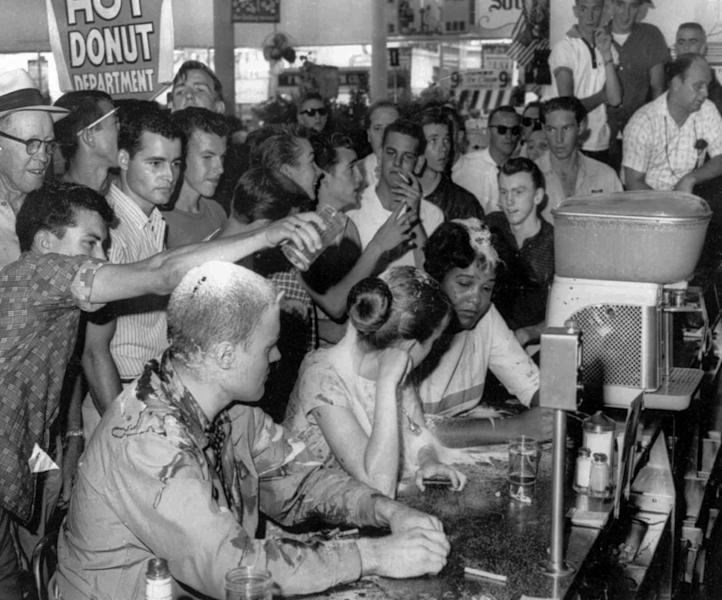 FILE - In this May 28, 1963 file photograph, a group of whites poured sugar, ketchup and mustard over the heads of Tougaloo College student demonstrators at a sit-in demonstration at a Woolworth's lunch counter in downtown Jackson, Miss. Seated at the counter, from left, are Tougaloo College professor John Salter,and students Joan Trumpauer and Anne Moody. Mississippi is unveiling a marker Tuesday, May 28, 2013 that commemorates a civil rights protest 50 years ago at the downtown Jackson Woolworth's.(AP Photo/Jackson Daily News, Fred Blackwell, File)
