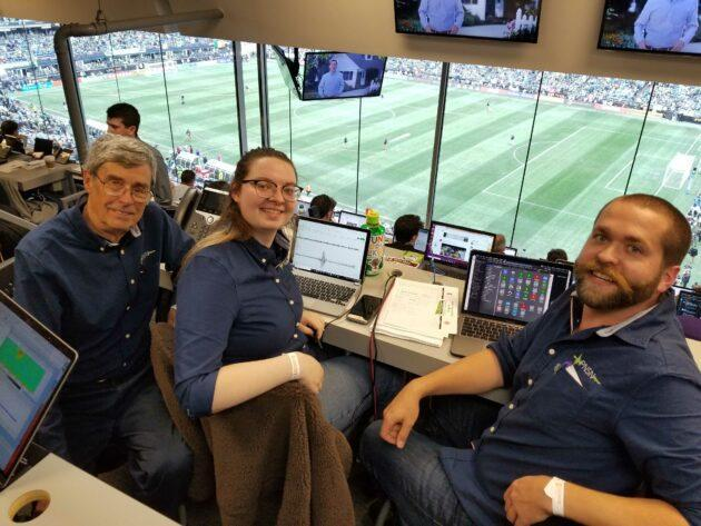 Members of the Pacific Northwest Seismic Network's team take up their stations for the Seattle vs. Toronto championship soccer match inside the press box at CenturyLink Field. From left are Steve Malone, Elizabeth Urban and Mickey Cassar. (GeekWire Photo / Taylor Soper)