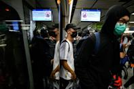 Protesters stood at doorways of trains, stopping them from closing, at a series of stations on the underground system (AFP Photo/Philip FONG)
