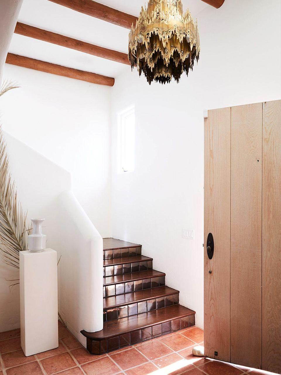 "<p>Simply no room for a console table? Try a pedestal instead. In this contemporary Santa Barbara adobe home designed by <a href=""https://www.corinnemathern.com/"" rel=""nofollow noopener"" target=""_blank"" data-ylk=""slk:Corrine Mathern Studio"" class=""link rapid-noclick-resp"">Corrine Mathern Studio</a>, it fits perfectly behind the stairs and adds that extra oomph without looking out of scale. It's the perfect ""entryway"" apartment solution when your front door opens up to your living room, kitchen, or even your bedroom. </p>"