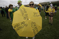 A woman holds an umbrella marked with pro-military phrases in Portuguese, during a rally backing President Jair Bolsonaro's anti-coronavirus-lockdown stance, marking May Day, or International Workers' Day, in Brasilia, Brazil, Saturday, May 1, 2021. (AP Photo/Eraldo Peres)