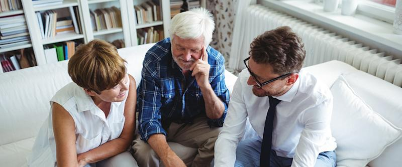 Senior couple speaking with advisor in living room