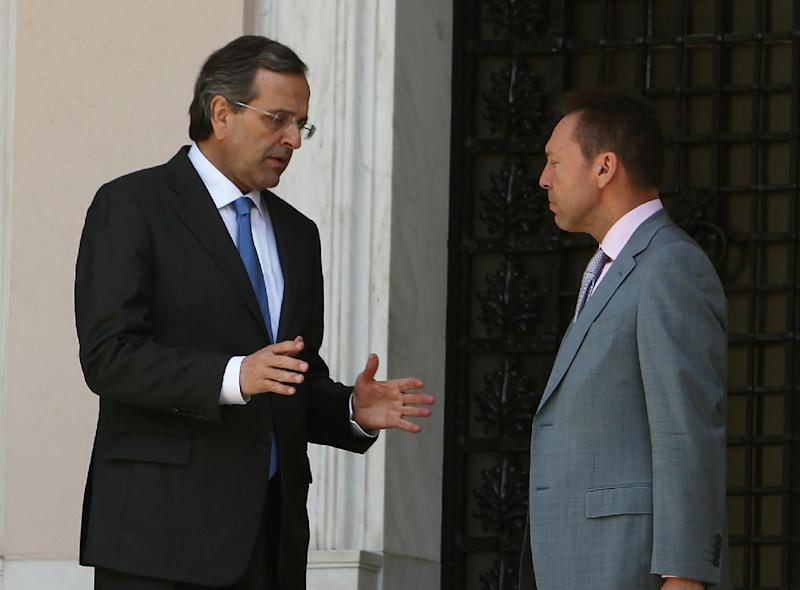 """Greece's Prime Minister Antonis Samaras, left, and Finance Minister Yannis Stournaras talk after a meeting with the heads of the two junior coalition parties at Maximos Mansion in Athens, Thursday, Sept. 27, 2012. Stournaras says the heads of the three parties in the governing coalition have reached a """"basic agreement"""" on an austerity package for 2013-14.The cuts are essential if Greece is to continue receiving funds from international emergency loans. (AP Photo/Thanassis Stavrakis)"""