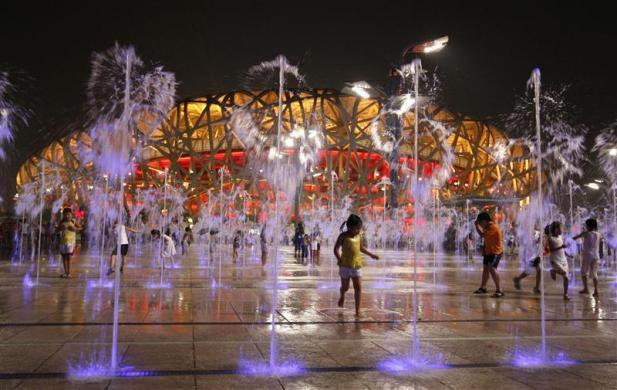 Children play in water fountains next to the National Stadium, also known as the Bird's Nest, during the Beijing 2008 Olympic Games, August 19, 2008.