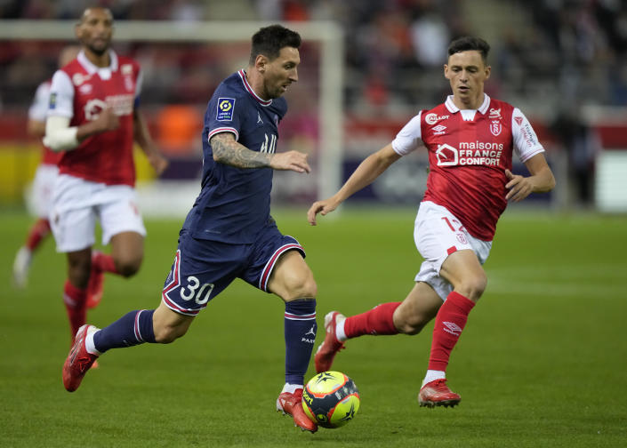 PSG's Lionel Messi, centre, controls the ball ahead of Reims' Xavier Chavalerin, right, during the France League One soccer match between Reims and Paris Saint-Germain, at the Stade Auguste-Delaune in Reims, France, Sunday, Aug. 29, 2021. (AP Photo/Francois Mori)