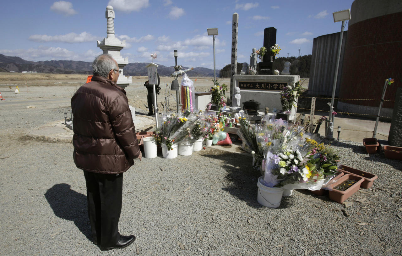 A man offers prayers in front of the main entrance of Okawa Elementary School where 74 of the 108 students went missing after the March 11 tsunami in Ishinomaki, Miyagi prefecture, Japan, Monday, March 11, 2013. The two-year anniversary Monday of Japan's devastating earthquake, tsunami and nuclear catastrophe is serving to spotlight the stakes of the country's struggles to clean up radiation, rebuild lost communities and determine new energy and economic strategies. (AP Photo/Shizuo Kambayashi)