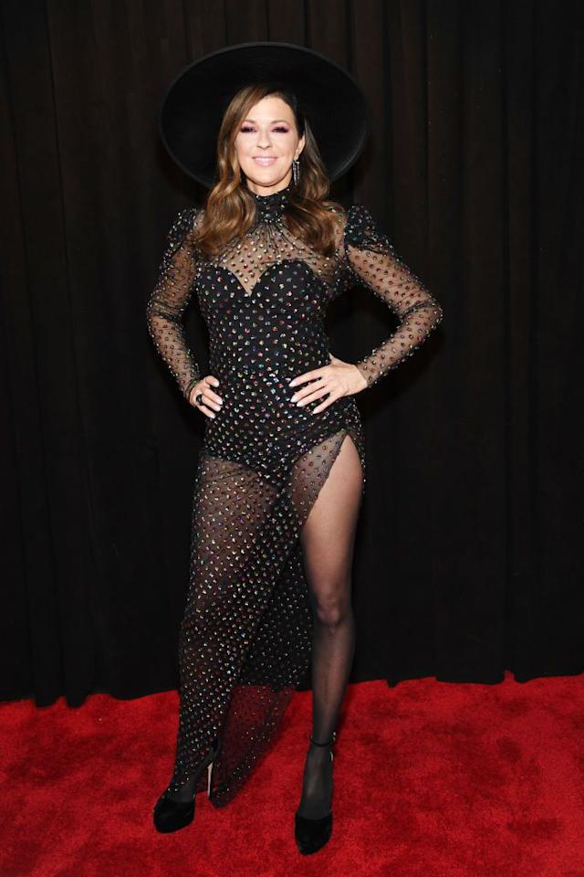 <p>In a studded black mesh gown with a hip-high slit. </p>