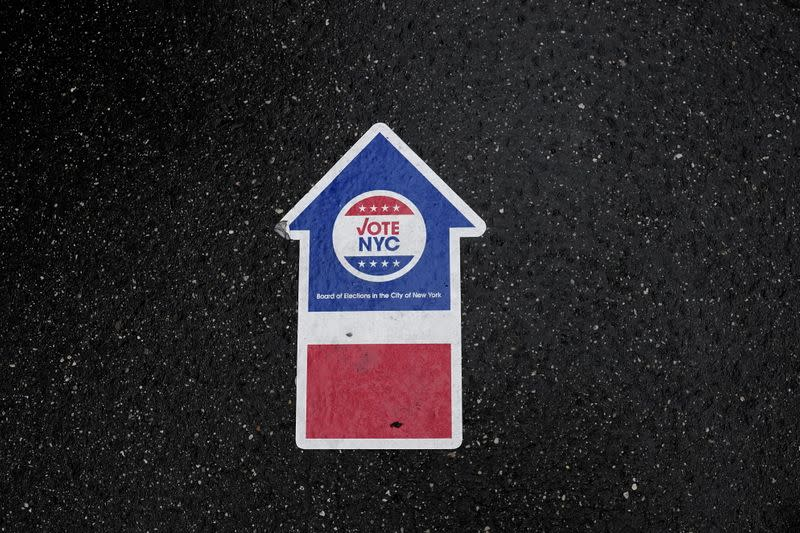 A sign on the ground directs people who line up in the rain to vote at an early site at Madison Square Gardens