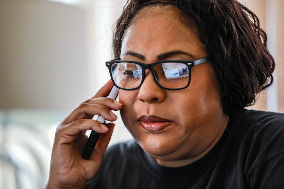 Christanine Brodis, 48, of Detroit talks on the phone with a representative from the Accounting Aid Society to help her file her 2020 taxes at her home on Feb. 13, 2021. Brodis lost her job as a personal home care provider and is struggling to get a tax refund from last year and she did not get one of her stimulus checks.