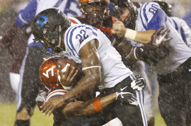 Duke running back Brittain Brown (22) slips past Virginia Tech defensive back Mook Reynolds (6) in the rain during the second half of an NCAA college football game in the rain in Blacksburg, Va., Saturday, Oct. 28, 2017. (AP Photo/Steve Helber)