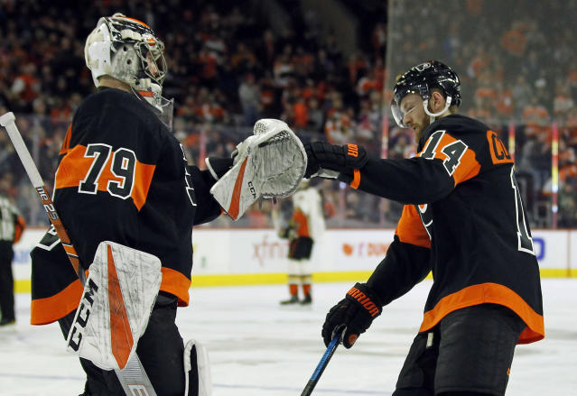 Philadelphia Flyers' Carter Hart, left, congratulates Sean Couturier on his goal during the first period of an NHL hockey game against the Anaheim Ducks, Saturday, Feb. 9, 2019, in Philadelphia. (AP Photo/Tom Mihalek)