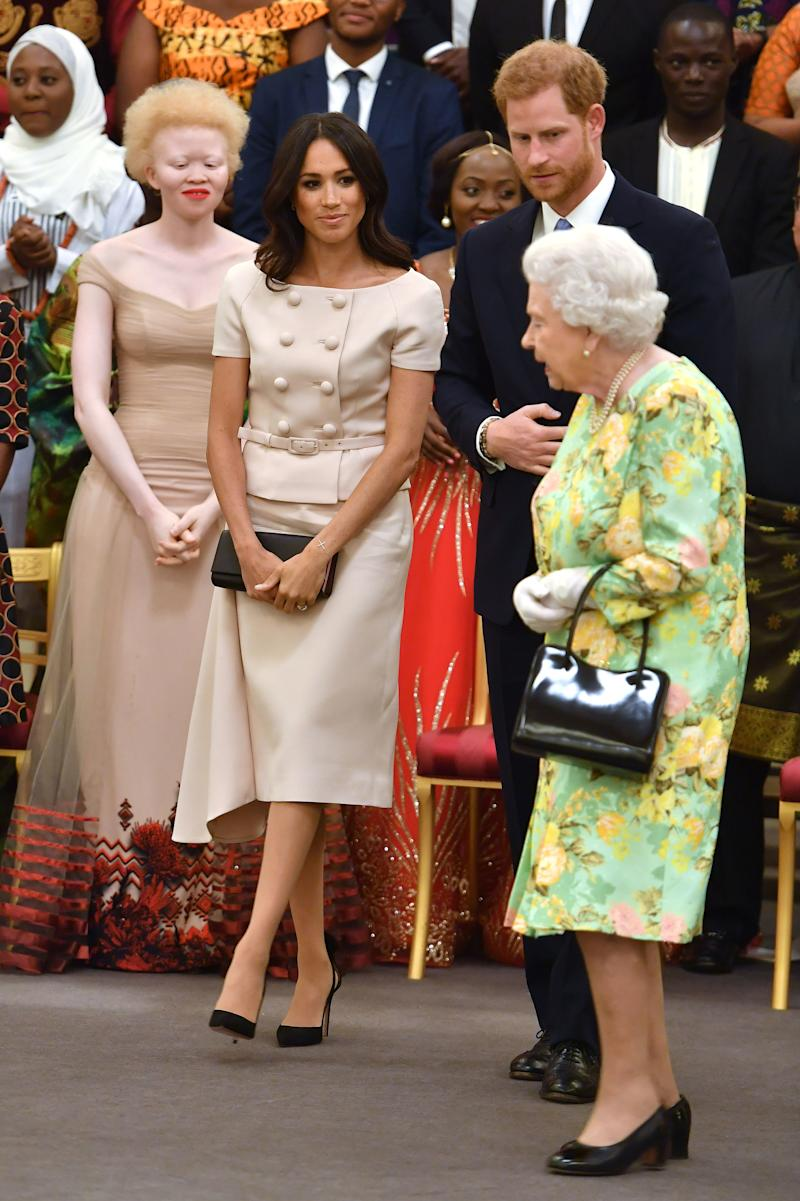 Meghan, Duchess of Sussex with Queen Elizabeth II and Prince Harry, Duke of Sussex at the Queen's Young Leaders Awards Ceremony at Buckingham Palace on June 26, 2018 in London, England.