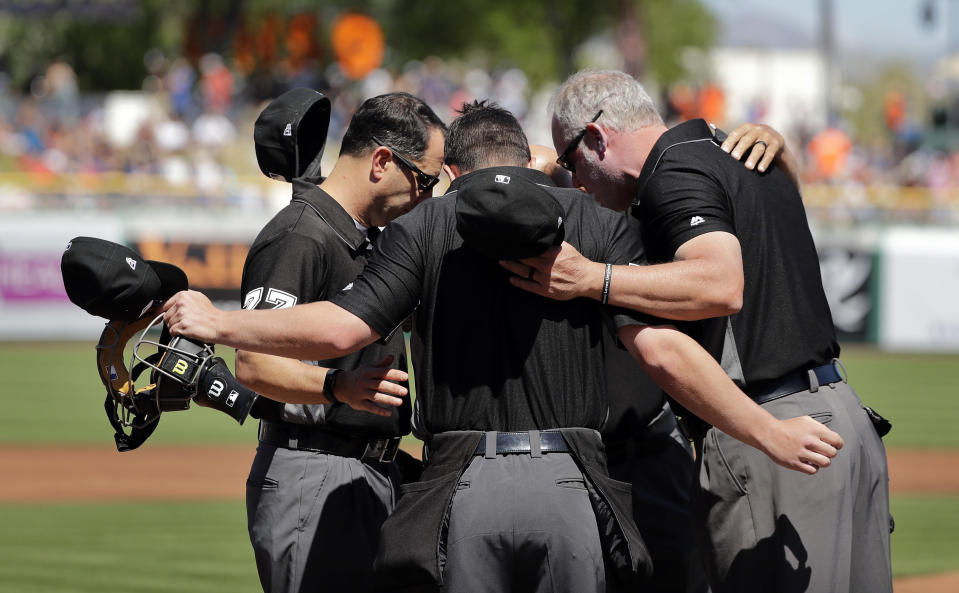 In this March 23, 2019 file photo umpires Jim Reynolds, left, Sean Ryan, Ted Barrett (hidden) and Kerwin Danley, right, huddle before a spring training baseball game between the San Francisco Giants and Arizona Diamondbacks in Scottsdale, Ariz. Major League Baseball and its umpires have reached a deal to cover a 2020 pay structure during the coronavirus pandemic, including a 50% cut in May and nothing more this year if no games are played. The sides struck an agreement late Thursday, April 30, 2020 two people told The Associated Press. (AP Photo/Elaine Thompson, file)