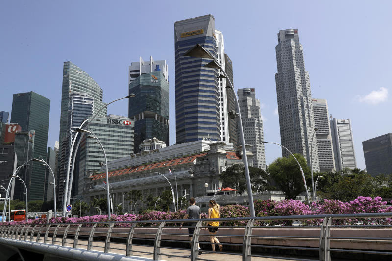 People walk along a footbridge in front of the financial district in Singapore, Thursday, June 7, 2018, in Singapore. U.S. President Donald Trump and North Korean leader Kim Jong Un will meet at a luxury resort in Singapore next week for nuclear talks, the White House said Tuesday. (AP Photo/Wong Maye-E)
