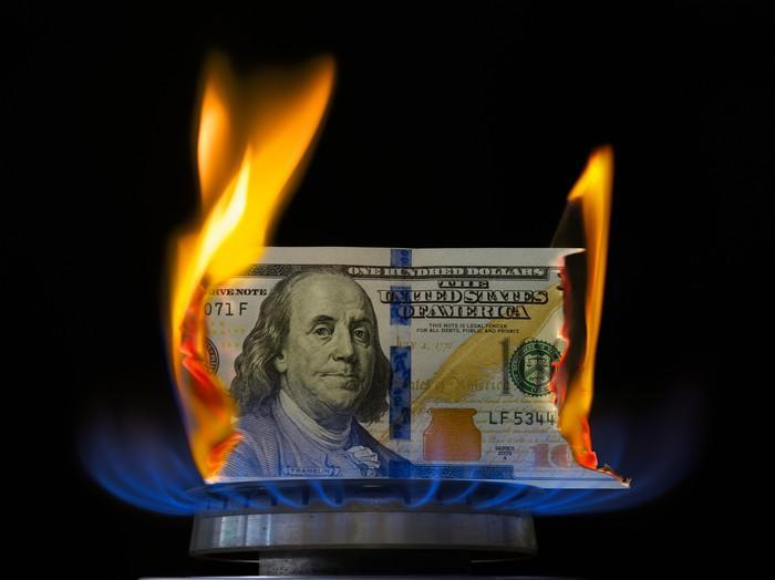 A one hundred-dollar bill on fire atop a lit stove burner.