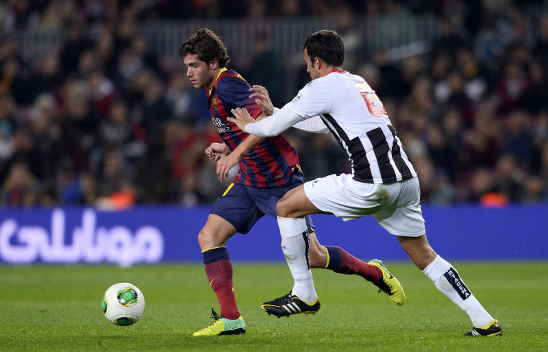 FC Barcelona's Sergi Roberto, left, duels for the ball against Cartagena´s Carlos David during a Copa del Rey soccer match at the Camp Nou stadium in Barcelona, Spain, Tuesday, Dec. 17, 2013. (AP Photo/Manu Fernandez)