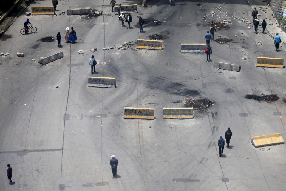 Pedestrians walk on a highway strewn with traffic barriers used by supporters of former President Evo Morales to block a highway in El Alto, Bolivia, Saturday, Nov. 16, 2019. Morales stepped down following nationwide protests over suspected vote-rigging in an Oct. 20 election in which he claimed to have won a fourth term in office. An Organization of American States audit of the vote found widespread irregularities. Morales has denied there was fraud. (AP Photo/Natacha Pisarenko)