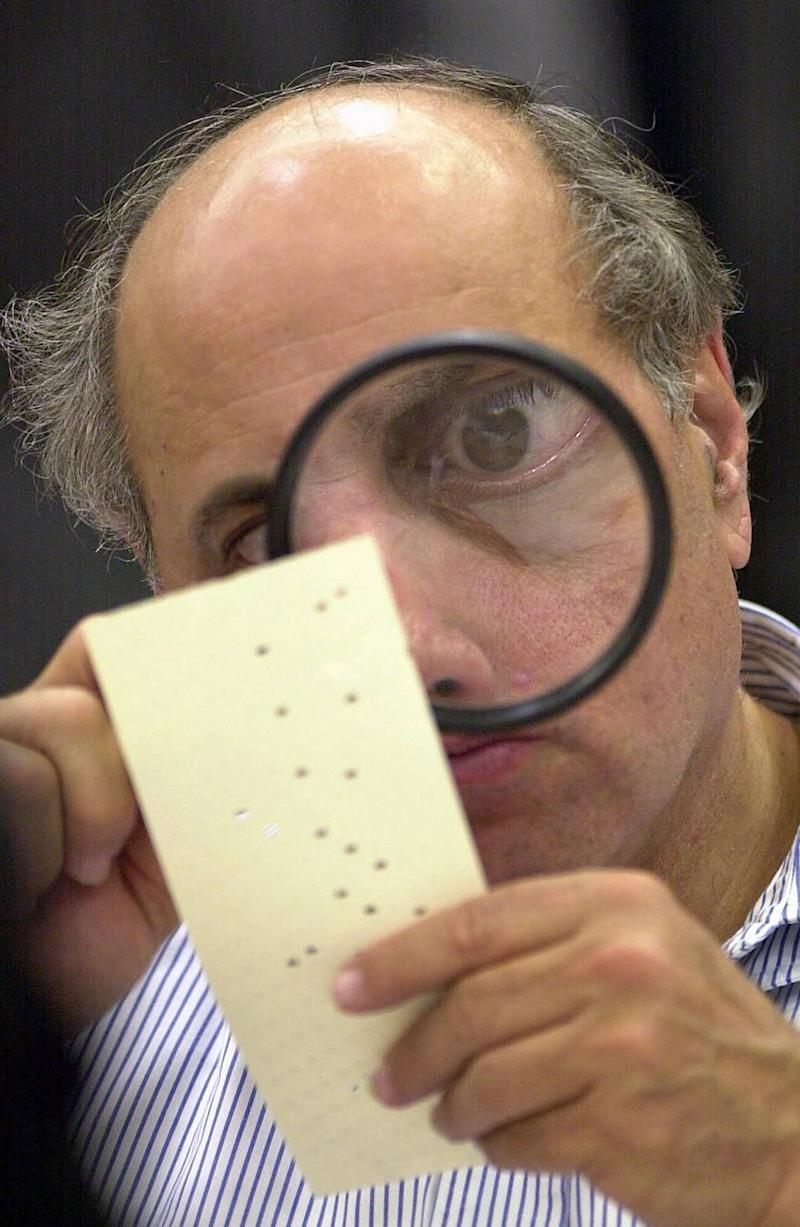 Broward County canvassing board member Judge Robert Rosenberg examines a disputed ballot in the 2000 election that became infamous for hanging chads and butterfly ballots. Following the election, Florida revised its election count laws and eliminated the punch card ballot in this photo from the Miami Herald file.