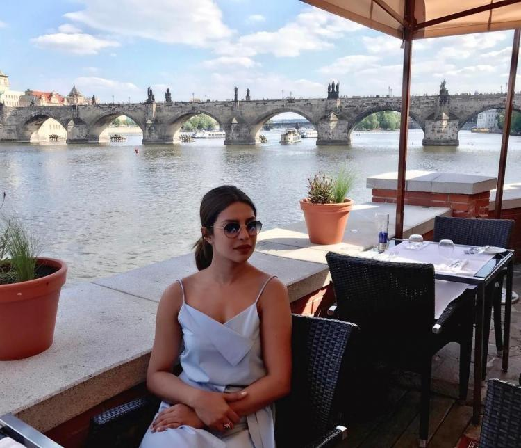 "<p>We informed you a few hours ago that the Bollywood star will be leaving for Prague and thanks to her new Instagram pictures, we know the actress has landed in the picturesque Prague.</p><p>In her new Insta snaps, the 34-year-old actress has channelled her inner vagabond and can be seen enjoying the view like any other traveller.</p><p>Recommended Read:  <a rel=""nofollow"" href=""https://www.pinkvilla.com/entertainment/news/380322/priyanka-chopra-next-victim-social-media-trolls-fans-allege-her-going?utm_source=yahoo&utm_medium=referral&utm_campaign=yahoomovies"">Priyanka Chopra next victim of social media trolls; fans allege her of going under the knife </a></p><p>In one picture, she can be seen sitting beside Vltava river in a restaurant and getting nostalgic. She captioned the pic as, ""Nostalgic.. the beautiful Vltava River #praguediaries.""</p><p>In another Instagram post, PeeCee can be seen posing with a huge statue and she captioned it as, ""Being a tourist.. #CharlesBridge #praguediaries in @camillaandmarc @tanyataylor @cristinaehrlich.""</p><p>Priyanka's first Prague pic was of a magnificent view. She wrote, ""Omgeeee beautiful view. Will keep u posted on my #praguediaries #nofilterneeded #makingnewmemories.""</p><p>The actress was juggling between her brand commitments, reading scripts and spending quality time with her family and friends in Mumbai. Priyanka will soon be heading to the US to start shooting for the third season of Quantico which will have 13 episodes.</p><p>She is also in talks to star in two Hollywood projects. One is A Kid Like Jake which stars Jim Parsons, Claire Danes and Octavia Spencer and the other is Isn't It Romantic which stars Rebel Wilson, Adam Devine and Liam Hemsworth. Priyanka is yet to give confirmation on both the Hollywood movies. </p>"