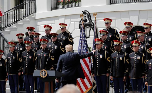 "U.S. President Donald Trump touches a member of the United States Army Chorus as he departs a ""celebration of America"" event on the South Lawn of the White House in Washington, U.S., June 5, 2018. The event was arranged after Trump canceled the planned visit of the Super Bowl champion Philadelphia Eagles to the White House. REUTERS/Carlos Barria"