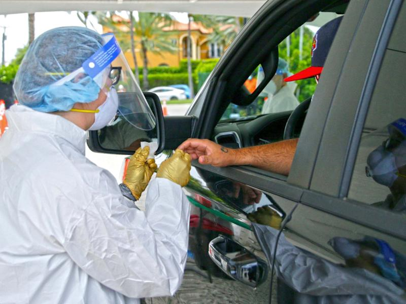A man is tested by a health worker at a coronavirus antibody test drive-through site in Bal Harbour, Florida, US, 13 May 2020: David Santiago/Miami Herald via AP