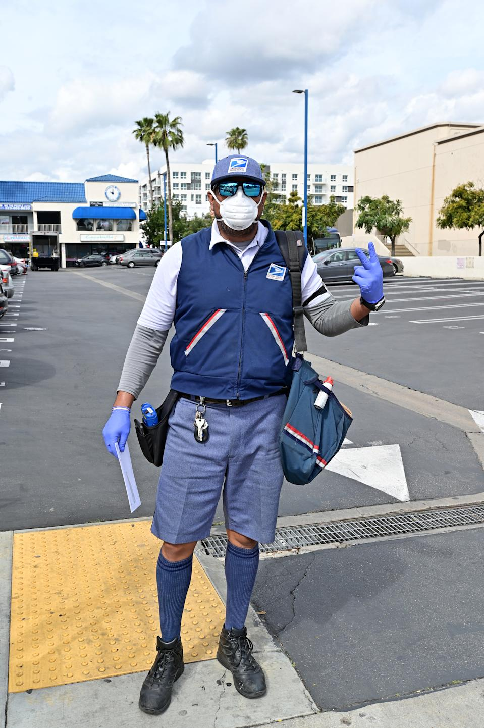 A Hollywood postal worker, dressed in protective mask and gloves, delivers the mail in Hollywood on Friday March 20th.. (Photo by Stephen Albanese/Michael Ochs Archives/Getty Images)