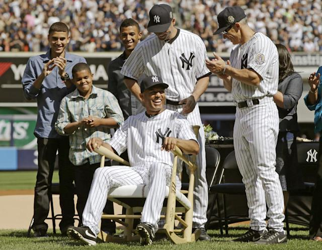New York Yankees manager Joe Girardi, far right, and Derek Jeter, center, above Rivera, watch as relief pitcher Mariano Rivera tries out a rocking chair they presented to him during a pregame ceremony at Yankee Stadium before a baseball game agains the San Francisco Giants, Sunday, Sept. 22, 2013, in New York. Rivera's three sons, Jafet, Jaziel and Mariano Jr. watch from left. AP Photo/Kathy Willens)