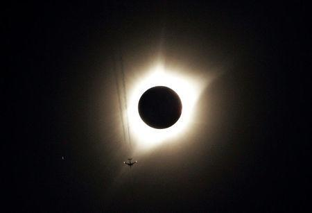 A jet plane flies by the total solar eclipse in Guernsey, Wyoming U.S. August 21, 2017. REUTERS/Rick Wilking