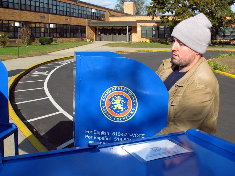 A.J. Scheuerman unloads voting machines outside Kramer Avenue Elementary School, Monday, Nov. 5, 2012, in Plainview, N.Y. The school will be one of Nassau County's polling places for the national elections being held on Tuesday. (AP Photo/Frank Eltman)