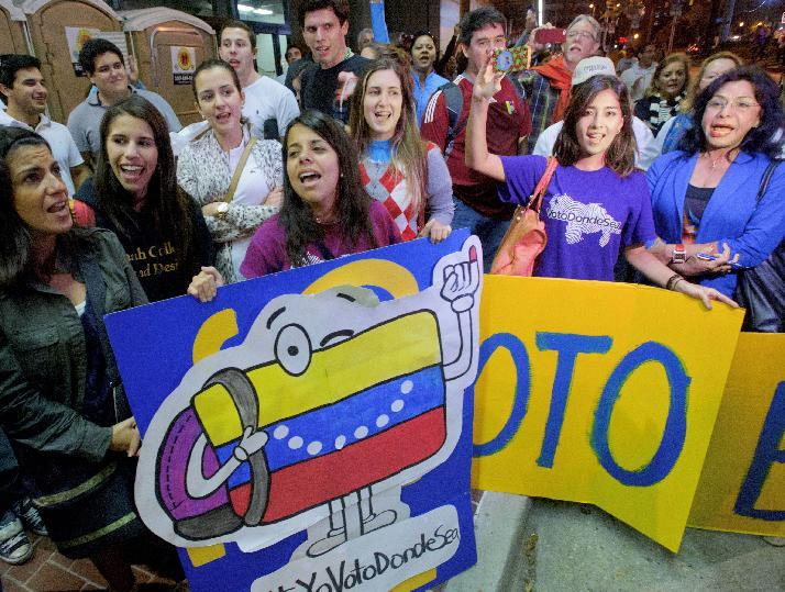 Venezuelan citizens living in the United States including Vanessa Dunn, left, holding Venezuela flag sign, and Lia Nunes, holding Voto (Vote) sign, from Miami, sing as they wait in line to vote at the New Orleans Ernest Morial Convention Center, in New Orleans, Sunday, Oct. 7, 2012. Hundreds of Venezuelans living in the U.S. streamed into New Orleans on Sunday to cast ballots in the presidential election in their homeland, many of them determined to end the 13-year reign of Hugo Chavez. With the country's consulate in Miami closed, thousands of Venezuelans traveled by bus, car and plane to cast their votes at the consulate in New Orleans.   (AP Photo/Matthew Hinton)