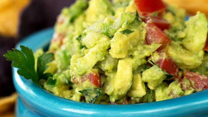 A bowl of fresh guacamole with corn tortilla chips.
