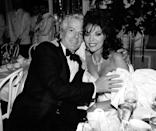 """<p>As her most famous character, Alexis Carrington in the television series Dynasty, Joan Collins dazzled viewers every week with her glamourous costumes, which always included heavy-set necklaces, weighty cocktail rings and shoulder-grazing earrings that more than held their own against her voluminous 1980s hairstyles. At the same time, Collins became a serious jewellery collector in her own right, and has cultivated an impressive collection of diamonds, pearls and Art Deco designs (not to mention sparkling five engagement rings) over the decades. </p><p>On 12 November, five of Collins' own precious pieces will be offered for auction during Bonhams' London Jewellery Sale to raise funds for one of her charities, the Shooting Star Children's Hospice, which cares for babies and children with life-limiting conditions, as well providing support for their families. </p><p>The pieces can all be viewed online <a href=""""https://www.bonhams.com/auctions/26567/"""" rel=""""nofollow noopener"""" target=""""_blank"""" data-ylk=""""slk:here"""" class=""""link rapid-noclick-resp"""">here</a> in advance, and include a spectacular necklace with a graduated series of brilliant and marquise-cut diamonds (which Collins can be seen wearing in the above photograph with Nicky Haslam), a pair of ruby pendant earrings, a corkscrew-shaped diamond brooch by Van Cleef & Arpels, a diamond collar and a pair of diamond earrings. </p><p>""""The fabulous thing about jewellery is how extraordinary it makes you feel – these pieces of jewellery have brought me so much joy over the years and I felt it was time for others to experience this,"""" Collins says. """"I am also delighted to support the Shooting Star Children's Hospice through part of the proceeds of the lots – the charity is vitally important, and it is an honour to be able to support it.""""</p><p>To celebrate the upcoming sale, we've rounded up some of Collins' most sparkling jewellery looks from the past few decades, both on- and off-screen. </p>"""