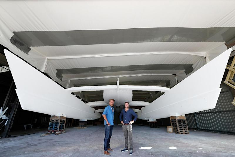 In this photo dated Aug. 31, 2016 and provided by RIVACom, Energy Observer expedition leader Jerome Delafosse, left, and captain, Victorien Erussard, pose in front of the two floats of Energy Observer, which is the first boat to be powered solely by renewable energies and hydrogen, in Saint Malo, western France. The first self-sufficient boat only powered by emission-free energy will start a six-year trip around the world next spring. (Pierrick Contin/Energy Observer via AP)