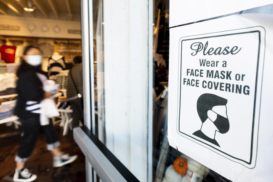 A shopper passes a sign urging customers to wear masks at a Brandy Melville store on Wednesday, Oct. 21, 2020, in San Francisco. As the coronavirus pandemic transforms San Francisco's workplace, legions of tech workers have left, able to work remotely from anywhere. Families have fled for roomy suburban homes with backyards. The exodus has pushed rents in the prohibitively expensive city to their lowest in years. (AP Photo/Noah Berger)